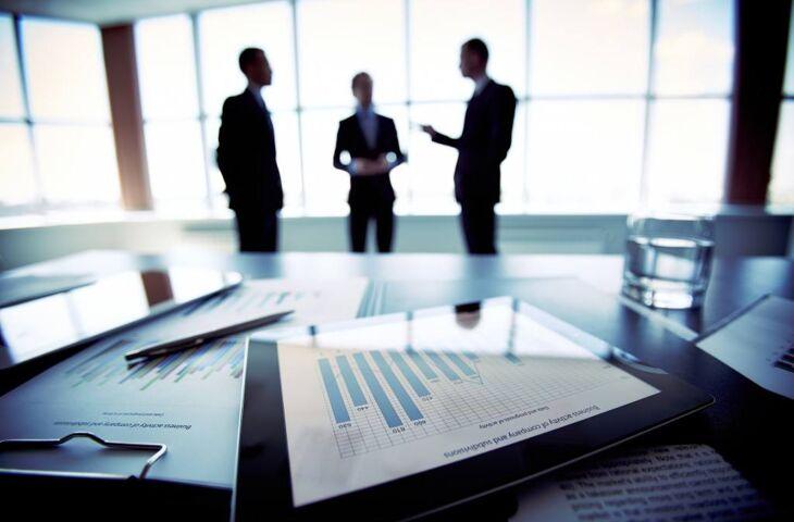 Um tablet com gráficos em primeiro plano e três executivos ao fundo